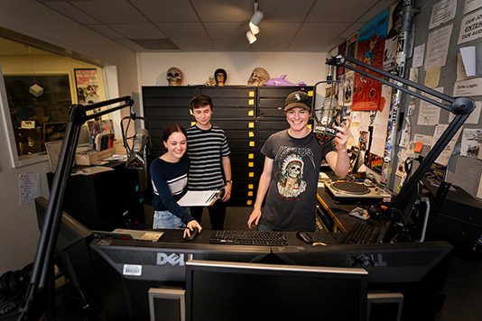Three KCPR DJs laugh at the radio station in February 2020.