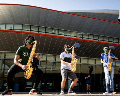 Three members of Mustang Band play the saxophone while wearing face coverings