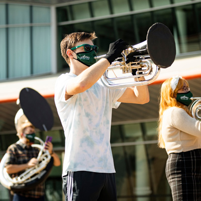 A member of the Cal Poly Band wears a mask while playing an instrument with MERV-13 filtration material on the bell cover