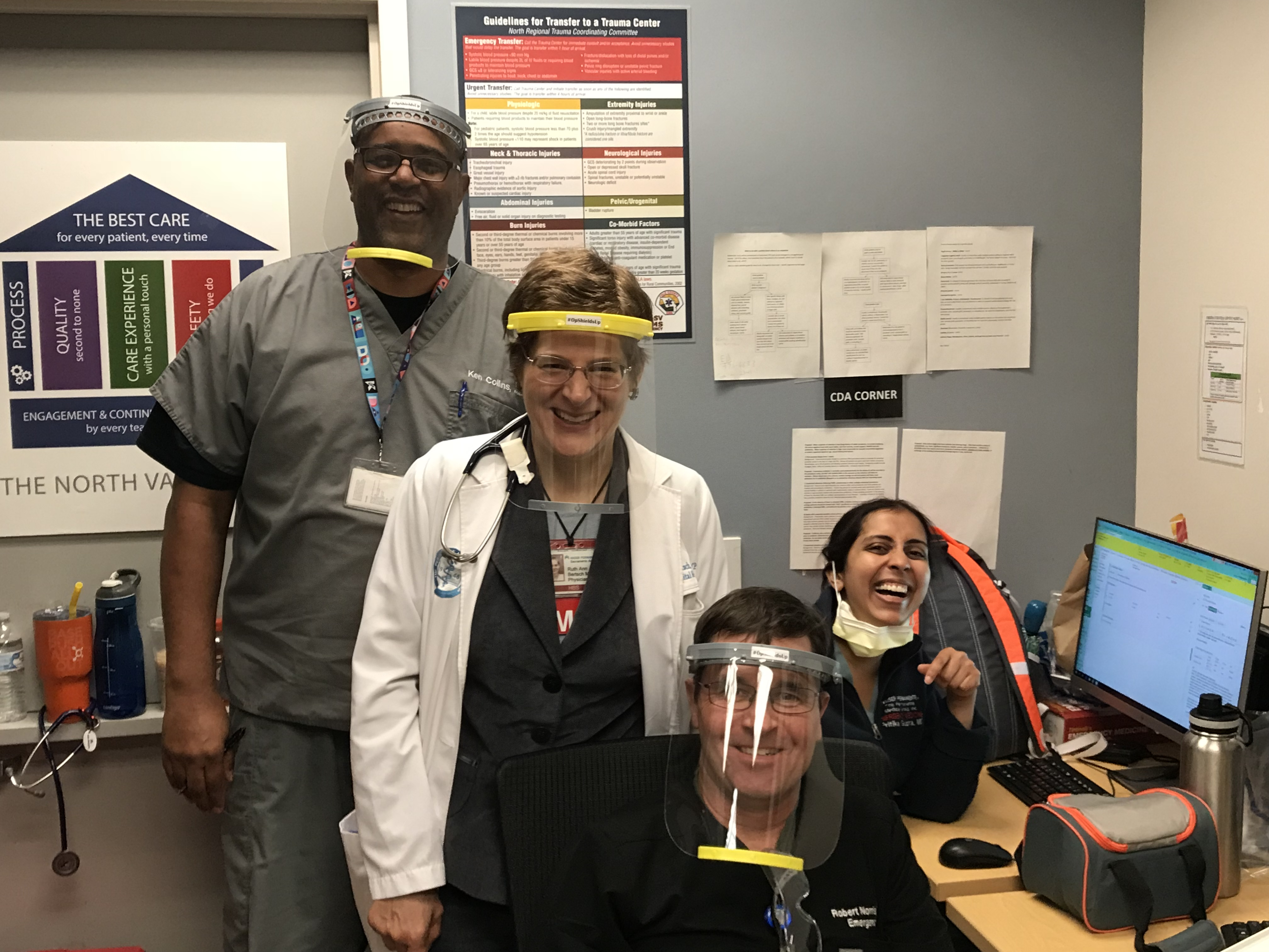 Four doctors wearing protective face shields.
