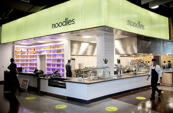 "A lit-up food counter decorated with jars of pasta and topped with a sign reading ""Noodles"""