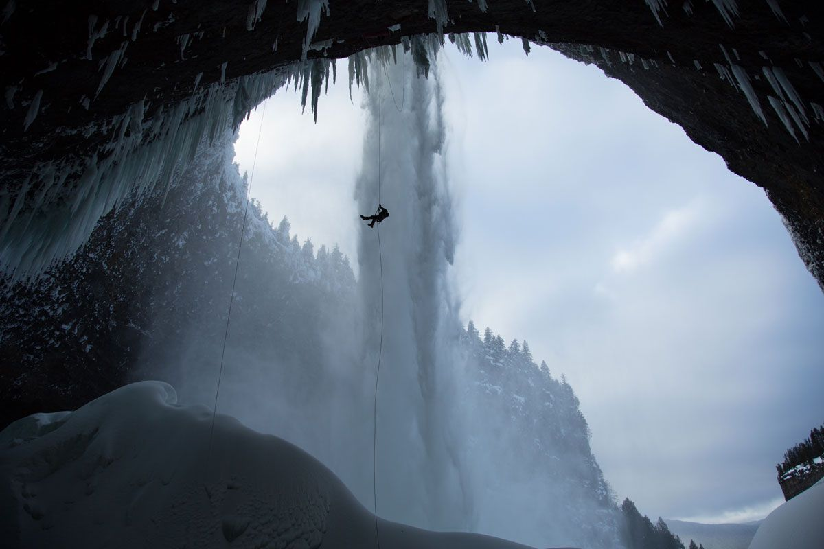 Rappelling Climber over Icy Mountain