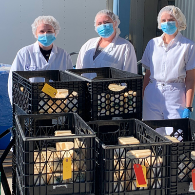 Three people in hairnets and face masks stand behind crates of food.