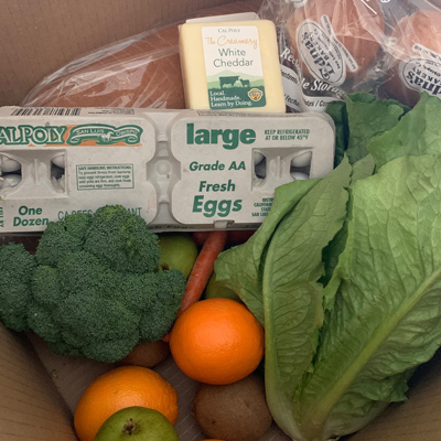 A food box including Cal Poly cheese, eggs and produce