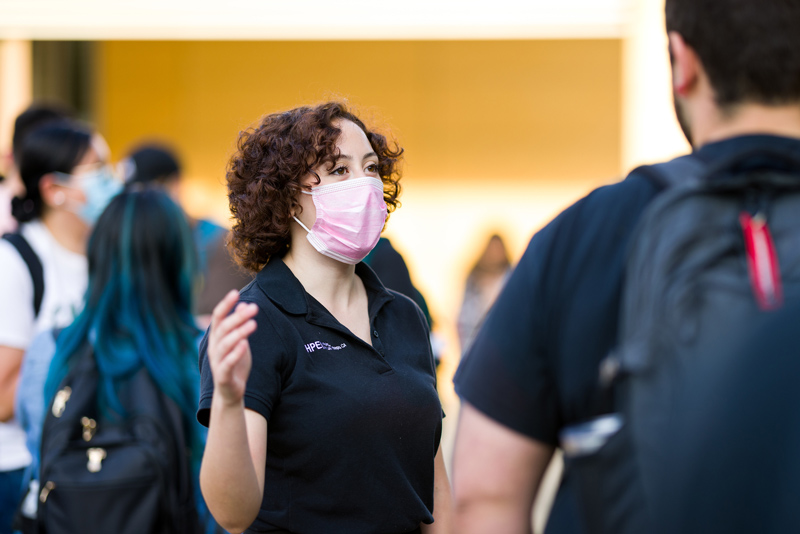 A person in a mask and black polo shirt speaks to a fellow student