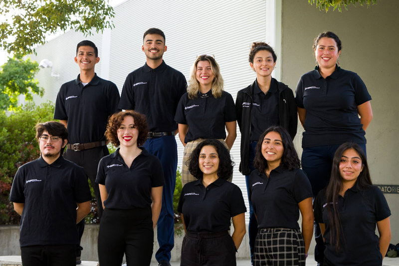 Ten Society of Hispanic Professional Engineers board members stand in black polo shirts