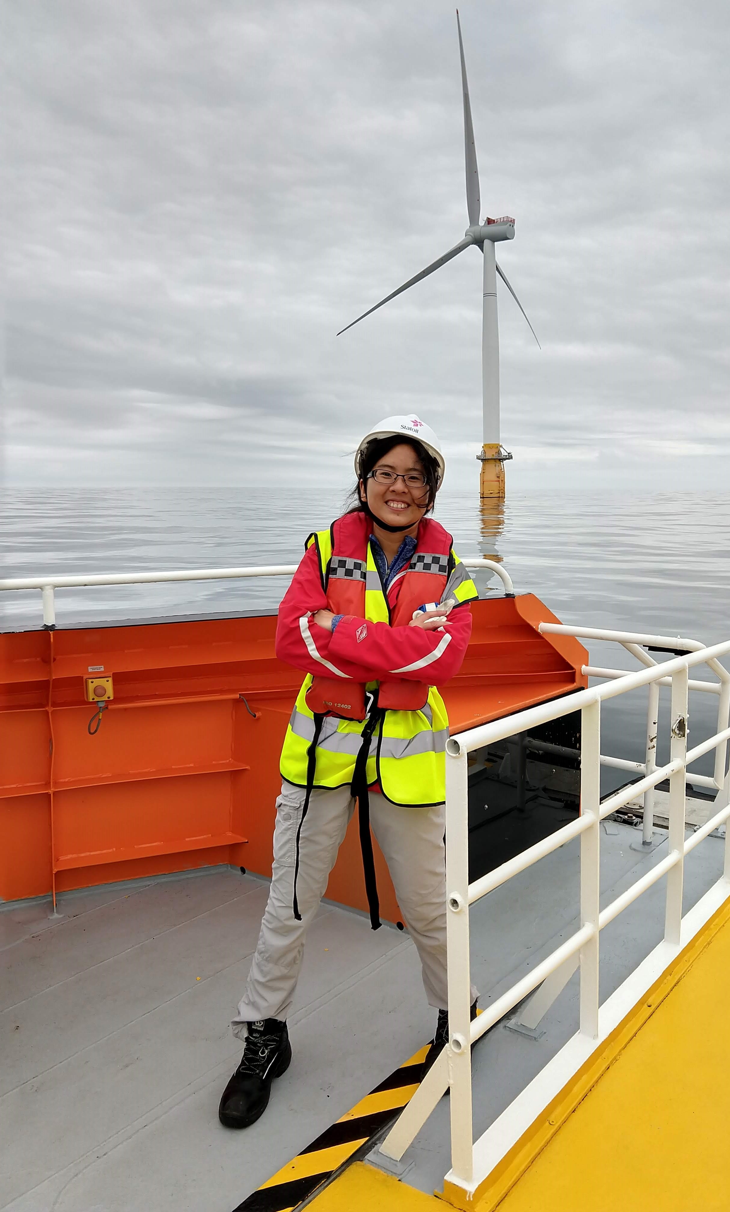 Researcher Yi-Hui Wang, in an orange life vest, on the deck of a boat in front of an offshore wind turbine