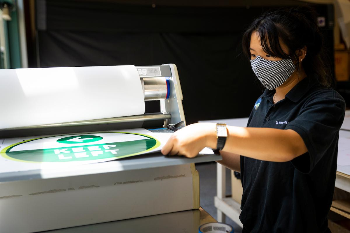 Michaela Kwan laminates a newly printed sign as she and other student employees print signage to be used in buildings on campus during the coronavirus pandemic.