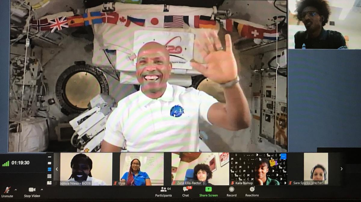 Victor Glover waves on a screenshot of a Zoom call with a space shuttle background. Seven smaller screens show students.