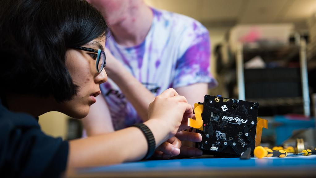 Student working on a cube satelite
