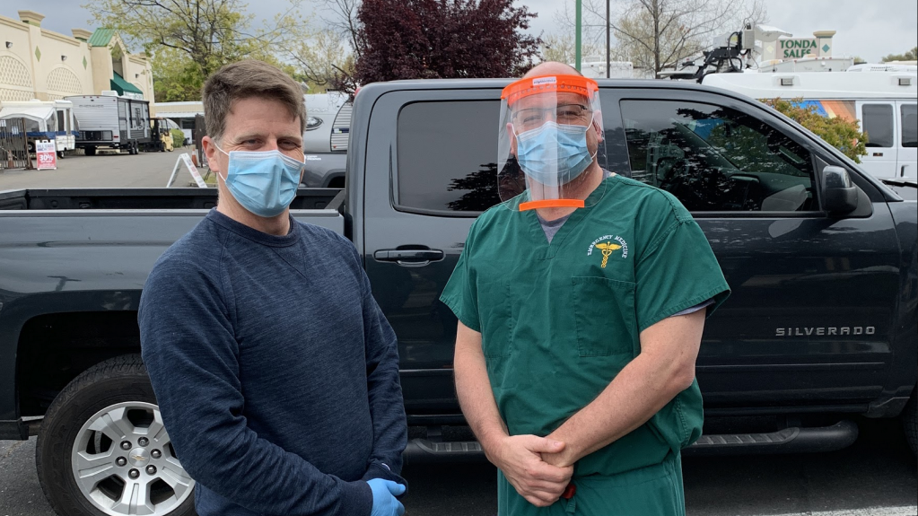 Alan Puccinelli, left, and a medical doctor, right, wear face shields and pose in front of a truck.