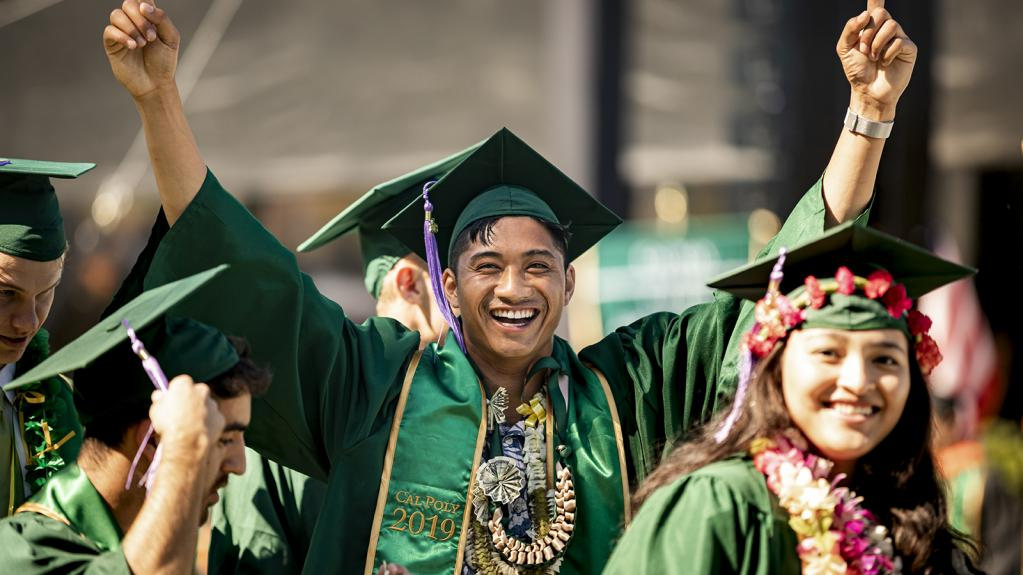 Student in cap and gown smiling and raising his hands in congratulations.