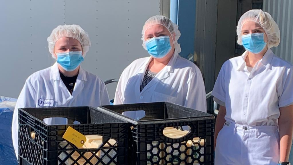 Three people wearing face masks and hair nets stand behind crates of food