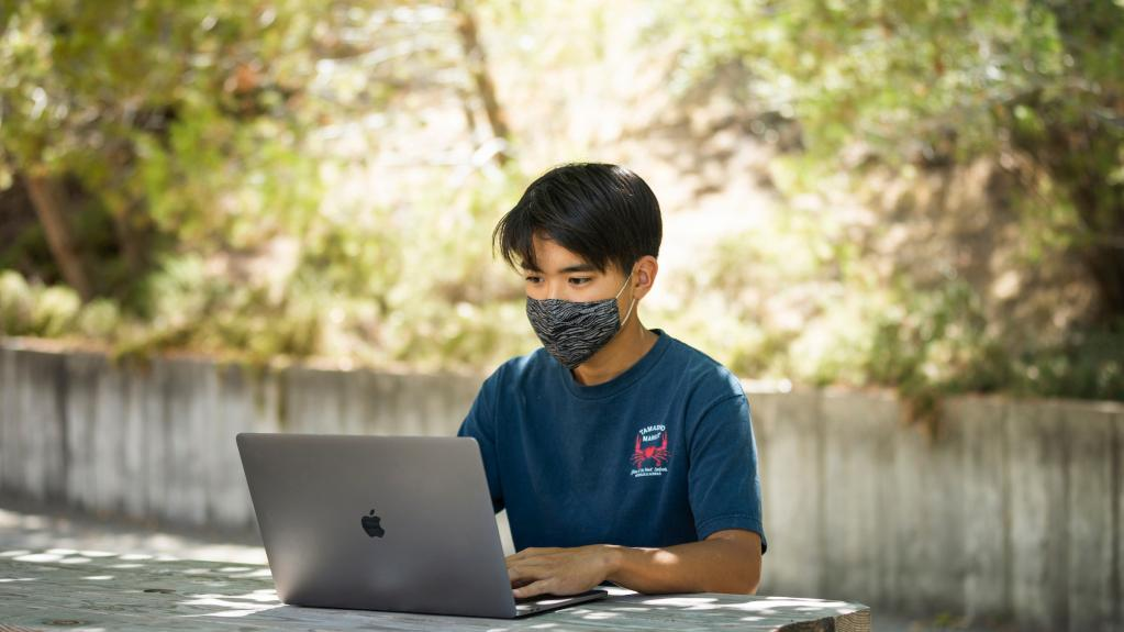 A student wearing a mask works at a laptop outside